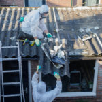 Professional asbestos removal. Man in protective suite removes asbestos roofing.